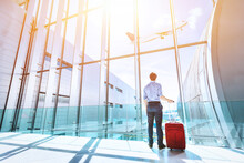Businessman At Airport Terminal Boarding Gate Looking At Airplane Flying