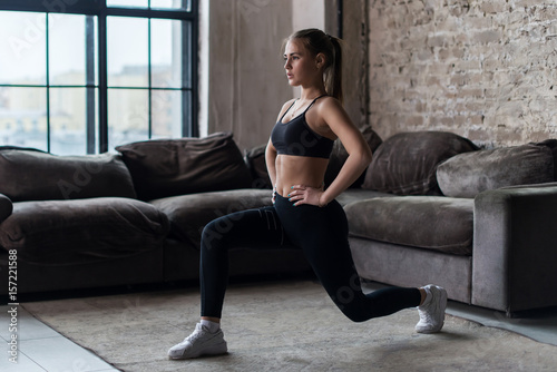 Canvas Print Pretty fit woman doing frontal lunges or squat exercise indoors in a flat
