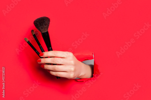 Photo  Crop female hand with cosmetic brushes