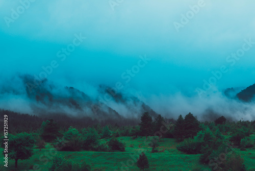 Keuken foto achterwand Turkoois Photo depicting beautiful a foggy mystic mountains. Fog clouds at the pine tree mystical woods, morning. Europe, mysterious alps landscape.