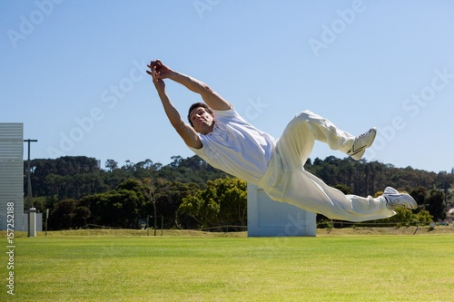 Photo  Full length of player diving to catch ball against blue sky