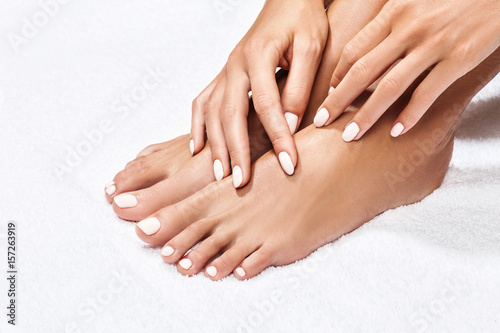 Poster Pedicure Beautiful female feet over white background.
