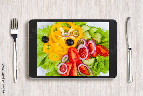 Fotografie, Obraz  black tablet pc with healthy food on screen and wooden table