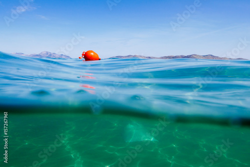 Fotografía  Marker buoy on surface of water. View half and half underwater.