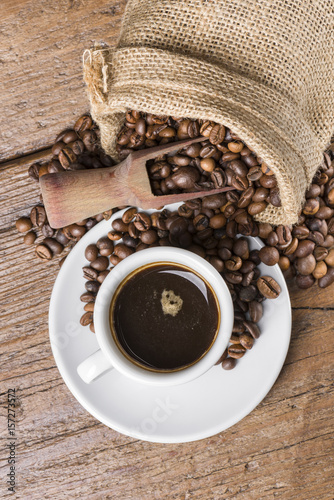 rustykalna-torba-pelna-ziaren-kawy-z-drewnianymi-i-filizanke-kawy-na-drewnianym-stole