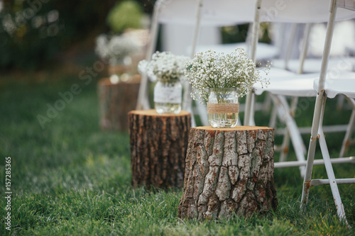 Billets of wood with bowls and flowers stand on the lawn
