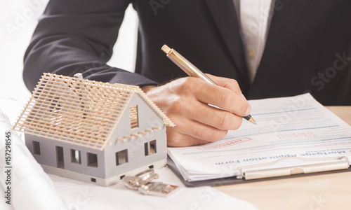 Fotografie, Obraz  Businessman signing a mortgage  contract  of a sale for a new house