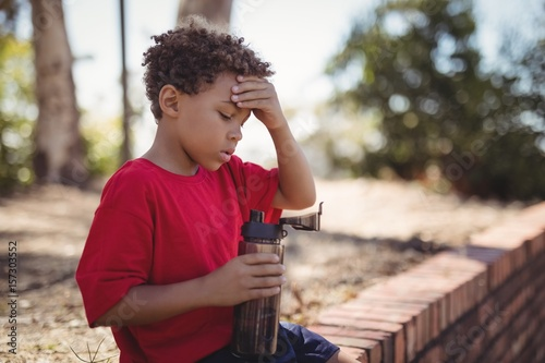 Dehydrated boy sitting with water bottle during obstacle course