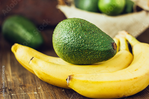 Avocado and banana over brown wooden background. © sharafmaksumov