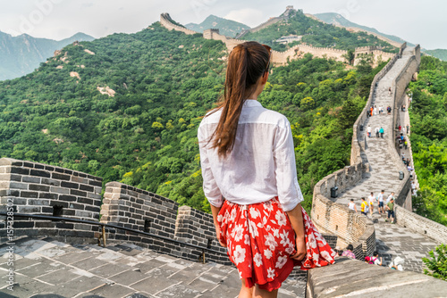 Poster Asian Famous Place Young girl tourist from behind looking at view of Great Wall of china at famous Badaling tourism attraction during travel vacation in Beijing. Asia summer holidays.