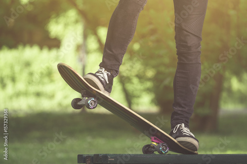 Zdjęcie XXL Skateboarder nogi przed skakać od ławki w parku
