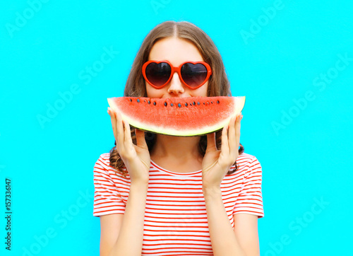 Fotografia  portrait happy young woman is holding slice of watermelon over colorful blue bac