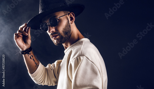 Cool stylish handsome man wearing sunglasses holding hat. Horizontal studio shot.