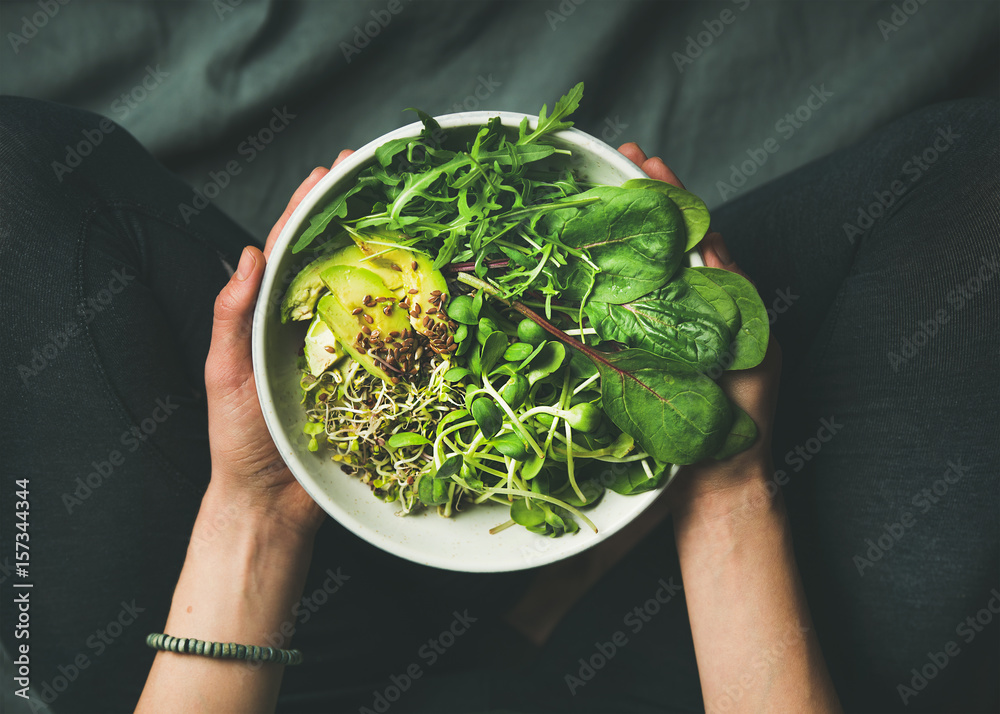Fototapety, obrazy: Green vegan breakfast meal in bowl with spinach, arugula, avocado, seeds and sprouts. Girl in leggins holding plate with hands visible, top view. Clean eating, dieting, vegan food concept