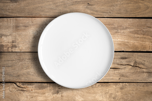 Top view of empty white food plate on a wood background.