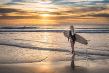 A Surfer Girl With Longboard At The Beach