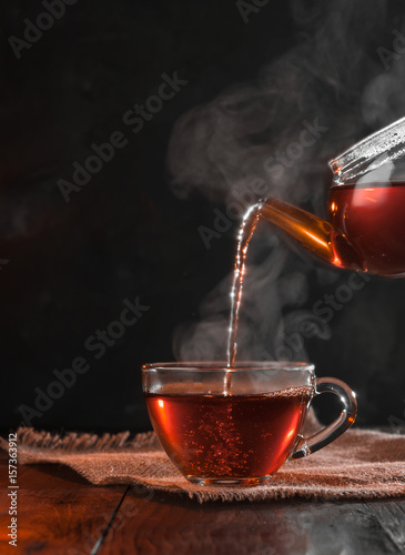 Deurstickers Thee Process brewing tea,tea ceremony,Cup of freshly brewed black tea,warm soft light, darker background.