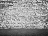 White grungy brick wall and dark asphalt floor