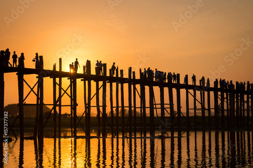 Leinwand Poster Silhouettes of people on U Bein bridge over the Taungthaman Lake at sunset, in A