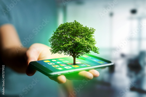 Fotografie, Obraz  Green tree going out of a smartphone - Ecology concept