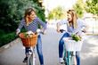 canvas print picture - Two young women exploring the city on bicycles