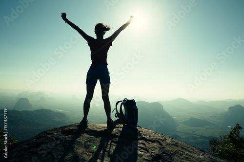 Valokuva  successful woman hiker open arms on sunrise mountain peak