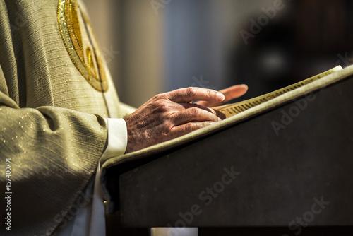 Fotografia Hands of catholic priest reading a bible.