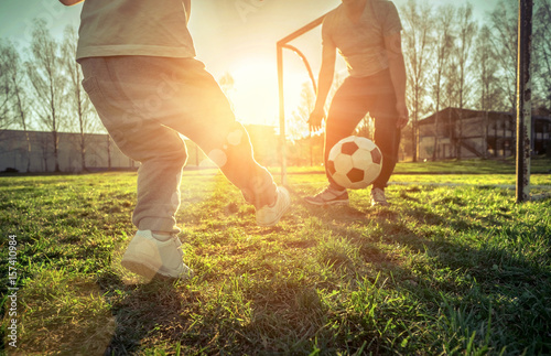 Father and son playing together with ball in football under sun