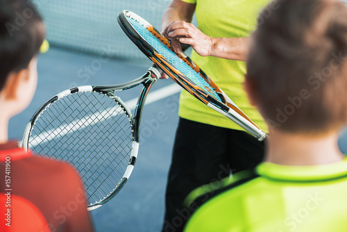 Trainer showing sports equipment to kids