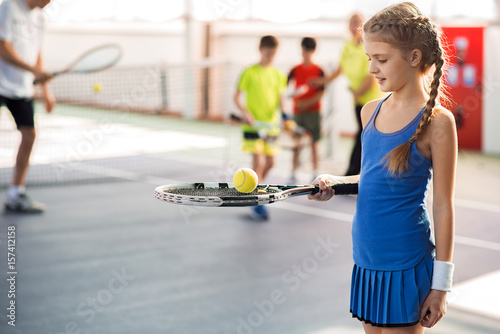 Happy female kid having fun with sports equipment