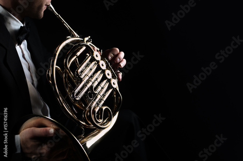 Foto auf Leinwand Musik French horn instrument. Player hands playing horn music instrument