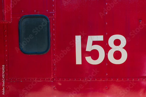 Fotografie, Obraz  Red metal texture with window and 158 number from train side