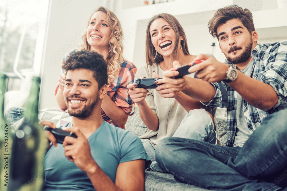 Fototapeta Young friends playing video games