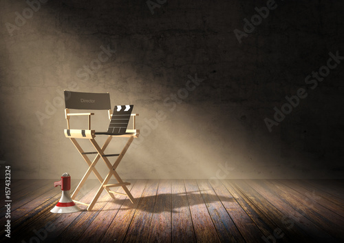 Fotografie, Obraz  Director's chair with clapper board and megaphone in dark room scene with spotli