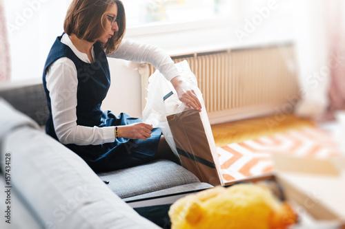 Plakat Młoda piękna kobieta na salonie sofa rozpakowuje unbox pudełko kartonowe zawierające nowe piękne ubrania