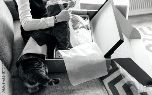 Plakat nowe buty, Kobieta rozpakowuje odpakowanie nowej paczki zawierającej modne ciuchy