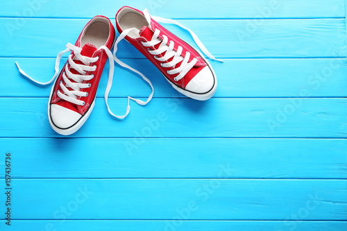 Pair of red sneakers on blue wooden table Tableau sur Toile