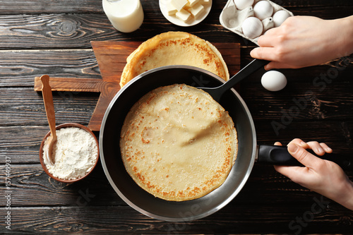 Woman cooking Russian pancakes in kitchen, closeup