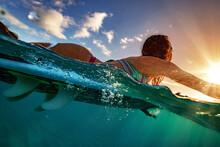 Surfer Girl Paddling On A Board At Sunset