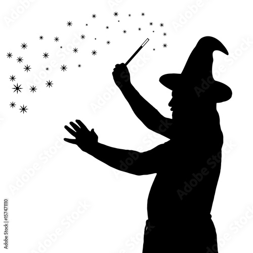 фотография Silhouette of bearded wizard in cloak with pointed hat creating magic