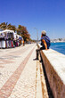 Älterer Mann sitzt am Hafen