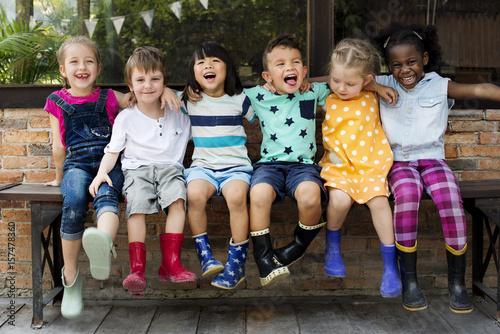 Valokuva  Group of kindergarten kids friends arm around sitting and smiling fun