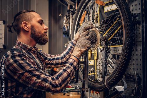 Zdjęcie XXL Mechanik usuwa rowerową tylną kasetę w warsztacie.