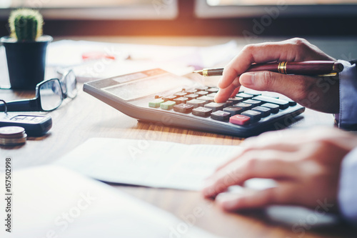 Fotografía  Businessman's hands with calculator and cost at the office and Financial data an