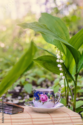 Staande foto Lelietje van dalen A small Cup of tea next to the flowers of lilies of the valley