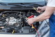Car mechanic using car battery jumper cable