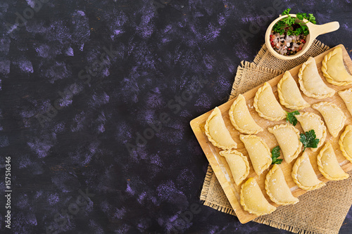 Photo  Delicious dumplings with cabbage on dark background. Top view