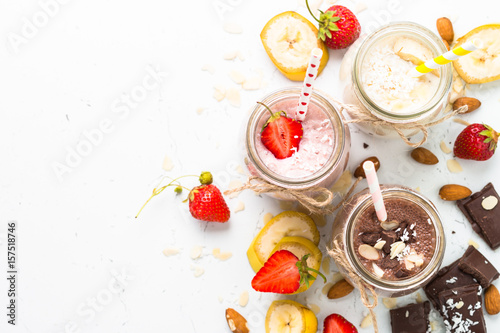 Fotografie, Obraz  Banana chocolate and strawberry milkshakes in jars on white