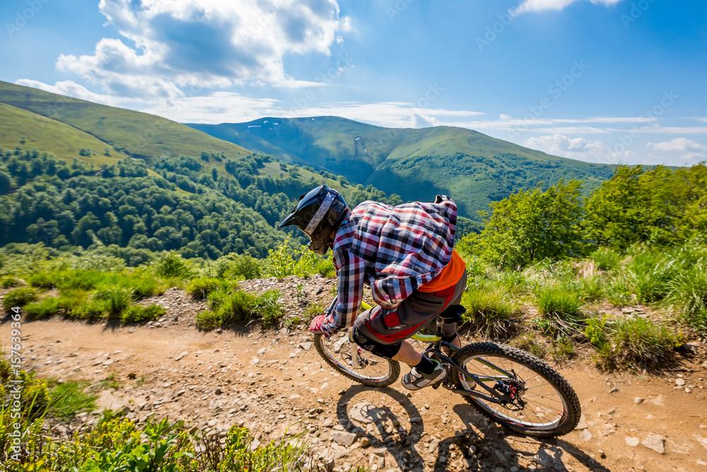 Ein Mann fährt Fahrrad, auf dem Hintergrund von Bergen und von ...