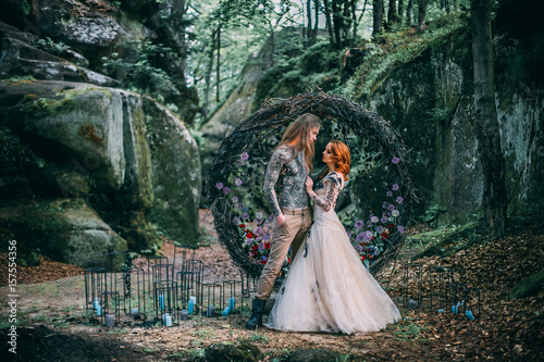 Fotografie, Tablou Beautiful young couple together near dark circle arch with flowers